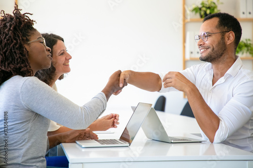 Smiling people talking and shaking hands at office Fototapeta
