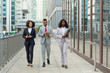 Full length of three business colleagues with documents and tablet going down city street. Business man and woman walking outside in city. Successful team concept