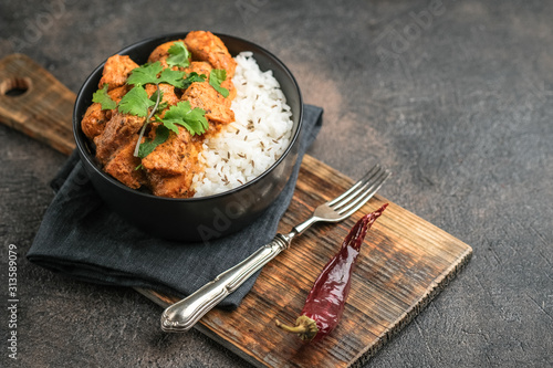 Fototapeta Chicken tikka masala traditional Asian spicy meat food with rice tomatoes and cilantro in a black bowl on dark background. obraz
