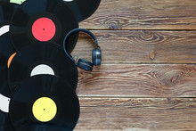 Retro Vinyl Discs Records And Headphones On Wood Table Background. Multicolored Labels. Top View. Place To Copy Space.