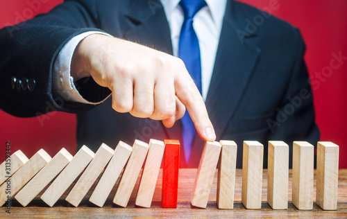 Photo Businessman restarts the process of falling dominoes