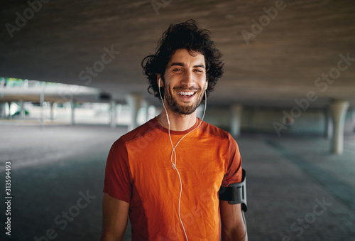 Cheerful portrait of a healthy sporty young man enjoying listening to music on earphones standing on city street