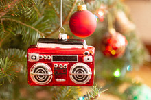 A Christmas Ornament In The Shape Of A Radio Or Boom Box Hanging On The Christmas Tree. Texture Added.