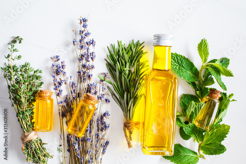 Obraz Essential oil in glass bottles. Thyme, mint, rosemary and lavender essential oils, top view. - fototapety do salonu