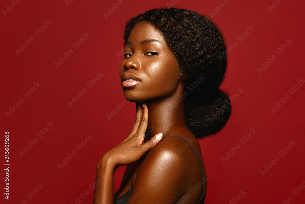 Fototapeta Fashion Beauty African American beautiful woman profile portrait. Brunette curly haired young model with dark skin  against red background