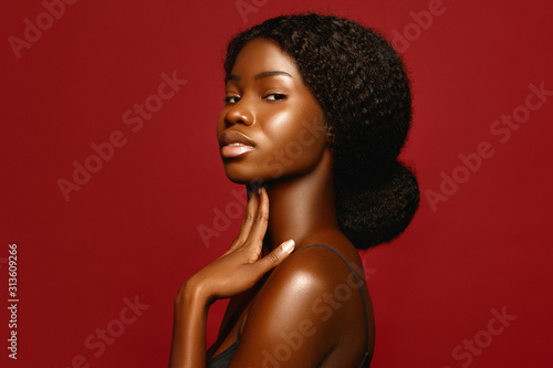 Obraz Fashion Beauty African American beautiful woman profile portrait. Brunette curly haired young model with dark skin  against red background - fototapety do salonu