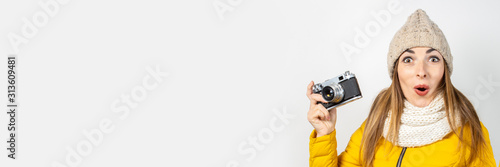 Young woman with a surprised face in a yellow down jacket and hat holds a camera in her hands on a light background Canvas-taulu