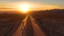 DRONE: Scenic Shot Of 18 Wheeler Trucks And Cars Crossing Mojave Desert At Dusk