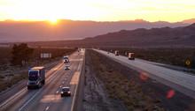 AERIAL: Scenic Shot Of 18 Wheeler Trucks And Cars Crossing Mojave Desert At Dusk