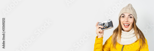 Fototapeta  Young woman with smile in a yellow down jacket and hat holds a camera in her hands on a light background