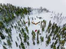 Aerial View Of Wooden Log Cabin Or Cottage In Snow  Winter Forest By The Lake In Rural Finland Lapland