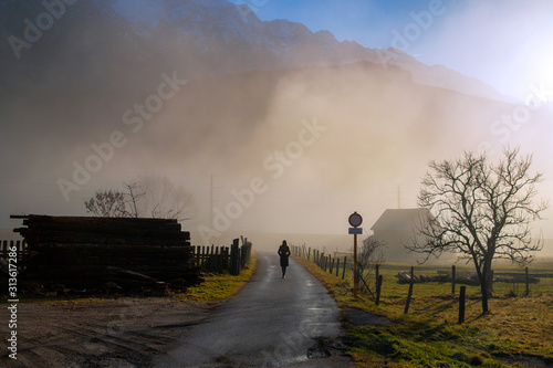 Photo Foggy melancholic countryside landscape with person silhouette walking alone on