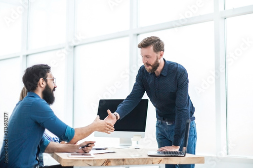 business people shaking hands over the Desk