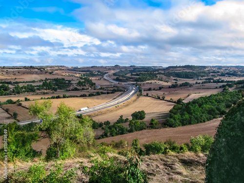 Valley in Catalonia with a zigzag motorway among brown fields. Beautiful autumn scenery of Spain from a hill in the village of Montfalco Murallat (Lleida, Catalonia)