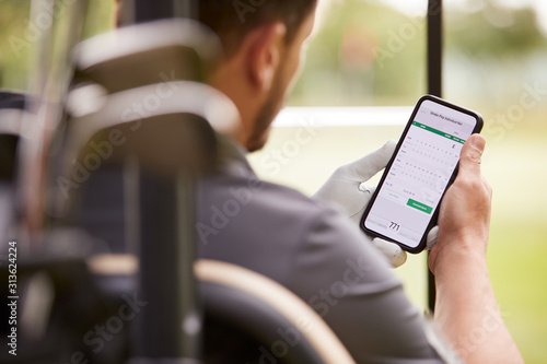 Obraz Close Up Of Male Golfer In Buggy Checking Score On Mobile Phone App - fototapety do salonu