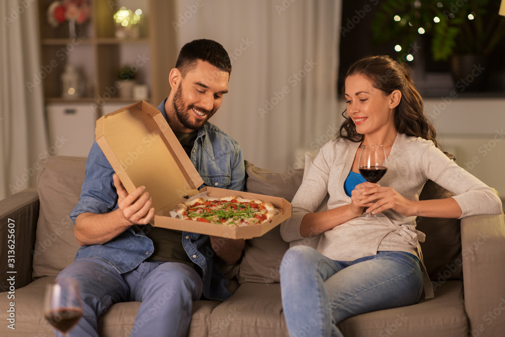 Fototapeta leisure, people and fast food concept - happy couple with wine eating takeaway pizza at home in evening