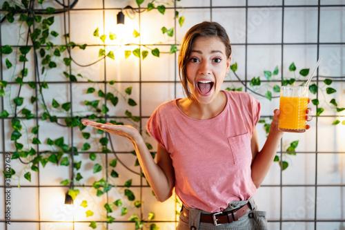 Fotografia Young beautiful woman enjoying a healthy raw fruit juice.