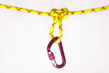 New Pink Oval Touristic And Alpinistic Carabine Hangs From Butterfly Loop Knot. Stretched Colored, Green Rope For Personal Belaying. Self-insurance Mustache. Isolated On White Background.