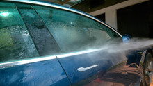 CLOSE UP: Water Is Sprayed Over Side Of A Blue Car Being Washed In The Driveway.