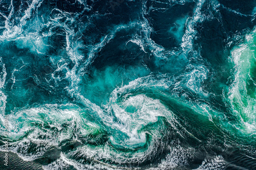 Fototapeta Abstract background. Waves of water of the river and the sea meet each other during high tide and low tide. Whirlpools of the maelstrom of Saltstraumen, Nordland, Norway obraz