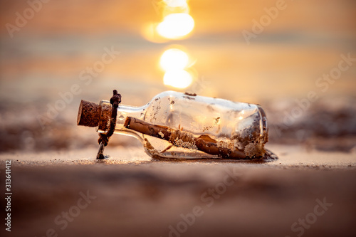 Message in the bottle against the Sun setting down Wallpaper Mural