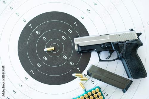 Obraz Guns with ammunition on paper target shooting   practice - fototapety do salonu