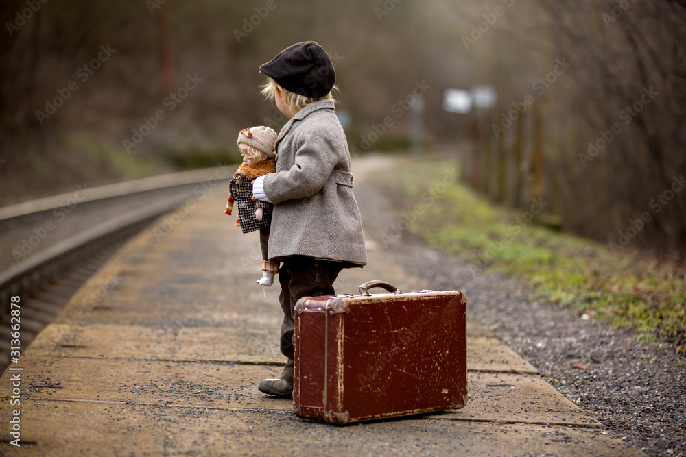 Fototapeta Adorable boy on a railway station, waiting for the train with suitcase and beautiful vintage doll...