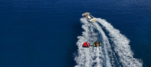 Aerial Drone Ultra Wide Photo Of Power Boat Towing Children Having Fun With Donut Water-sports In Deep Blue Mediterranean Bay
