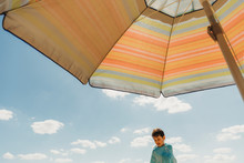 View From Under Parasol Of Boy Wrapped In Towel Against Blue Sky