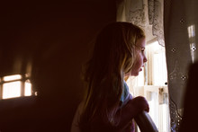 A Little Girl Looks Out A Bedr...