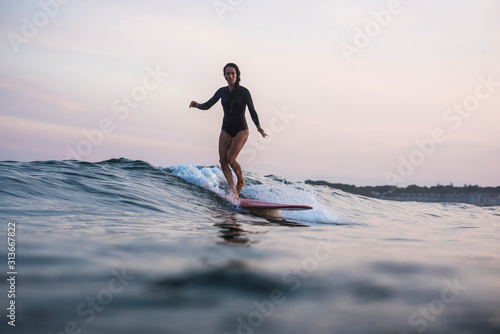 Water women friends surfing together at sunset - 313667822