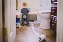 A Baby Boy Stands In A Bathroom With An Unfurled Toilet Roll.