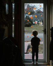 A Little Boy Looks Out A Glass Storm Door With Autumn Leaf Decals On I