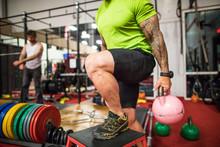 Macho Bodybuilder Holding Hot Pink Kettlebells At The Gym.