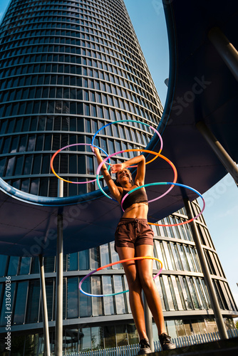 Woman performing Hula Hoop dance with five rings in city - 313670036