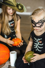 Two Sisters Dressed For Halloween In Skeleton Costumes With Pumpkins
