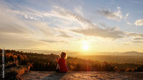 Obraz The boy enjoys the sunset in the mountains - fototapety do salonu