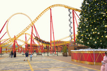 The Roller Coaster Ride With Thrill-seekers On The Background Of The New Year Tree. Christmas Holidays