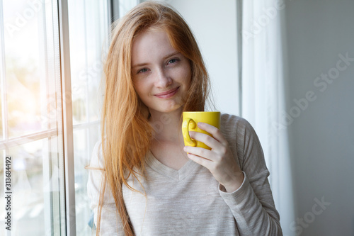 Obraz candid portrait of cheerful young smiling red hair woman holding yellow coffee cup, enjoying morning coffee and new day - fototapety do salonu
