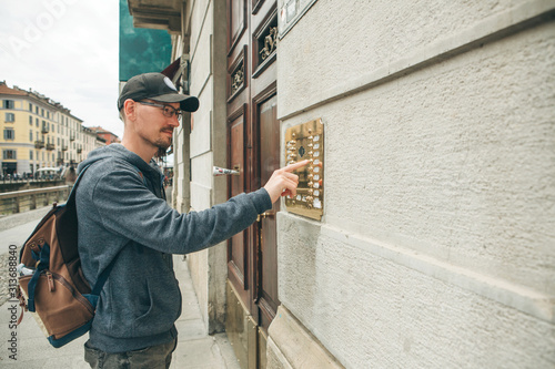 Obraz A guy or a man or a tourist presses a doorphone button to access inside. - fototapety do salonu