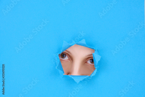 Fotomural  Part of a woman's face the eyes and nose of an attractive woman looking into camera, behind a broken wall or torn paper, on blue background