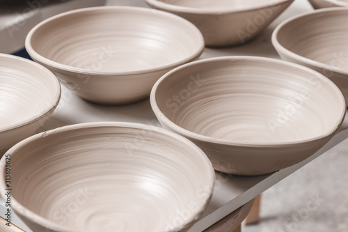raw ceramic bowls made from white clay on the potter's wheel circle waiting for Wallpaper Mural