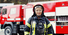 Portrait Of Young Woman Firefighter Standing Near Fire Truck. Fireman In Protective Suit With Oxygen Mask And Helmet.