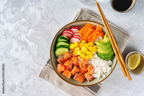 Top view of poke bowl with vegetables, rice and salmon