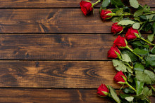 Red Roses On A Dark Wooden Bac...
