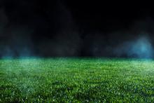 Spotlight Shining On The Green Turf Of An Empty Sports Field At Night.