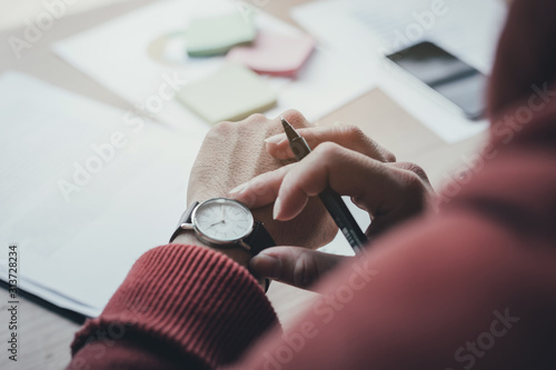 Fotografiet looking at luxury watch on hand check the time writing business information in notepad at workplace