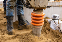 Closeup View Of A Person Operating A Vibratory Earth Rammer Compacting The Ground After Installation Of New Septic Tanks, Wearing Work Boots In Background