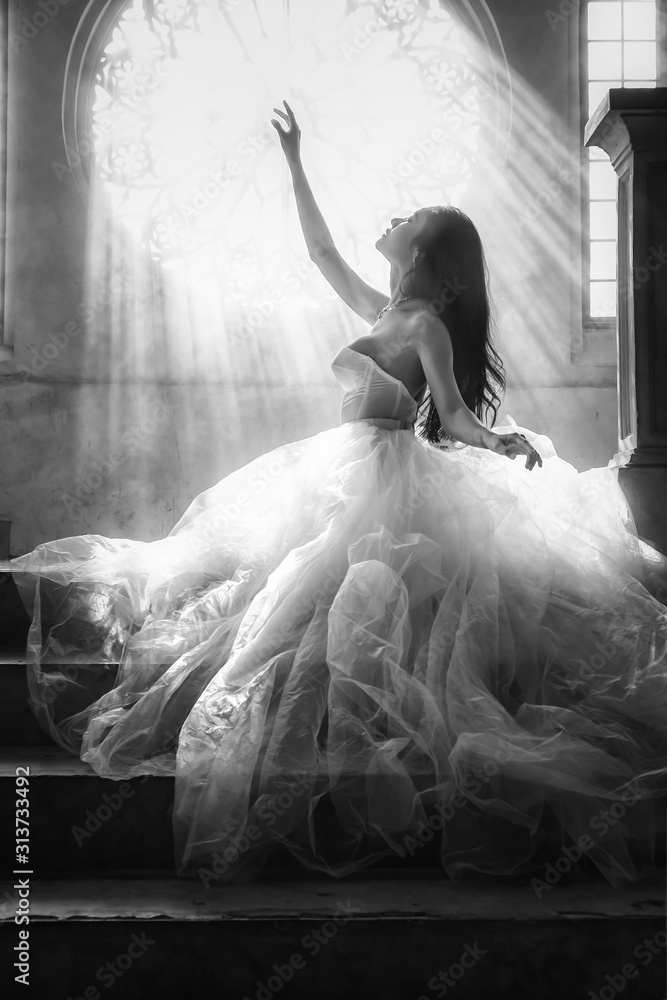 Fototapeta silhouette black and white portrait of bride in white dress sitting on stairs infrontof window with sunlight pass through