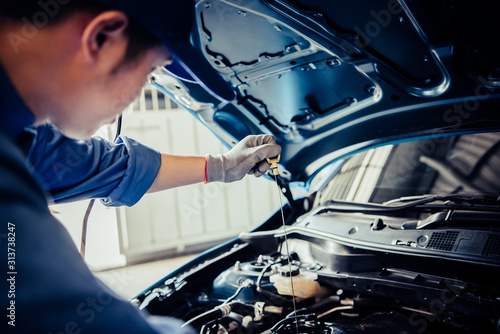 Fototapeta Car mechanic holding checking gear oil to maintenance vehicle by customer claim order in auto repair shop garage. Engine repair service. People occupation and business job. Automobile technician obraz